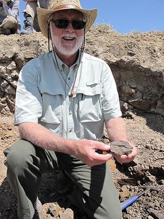 Secretary Clough and a fossil leaf he unearthed